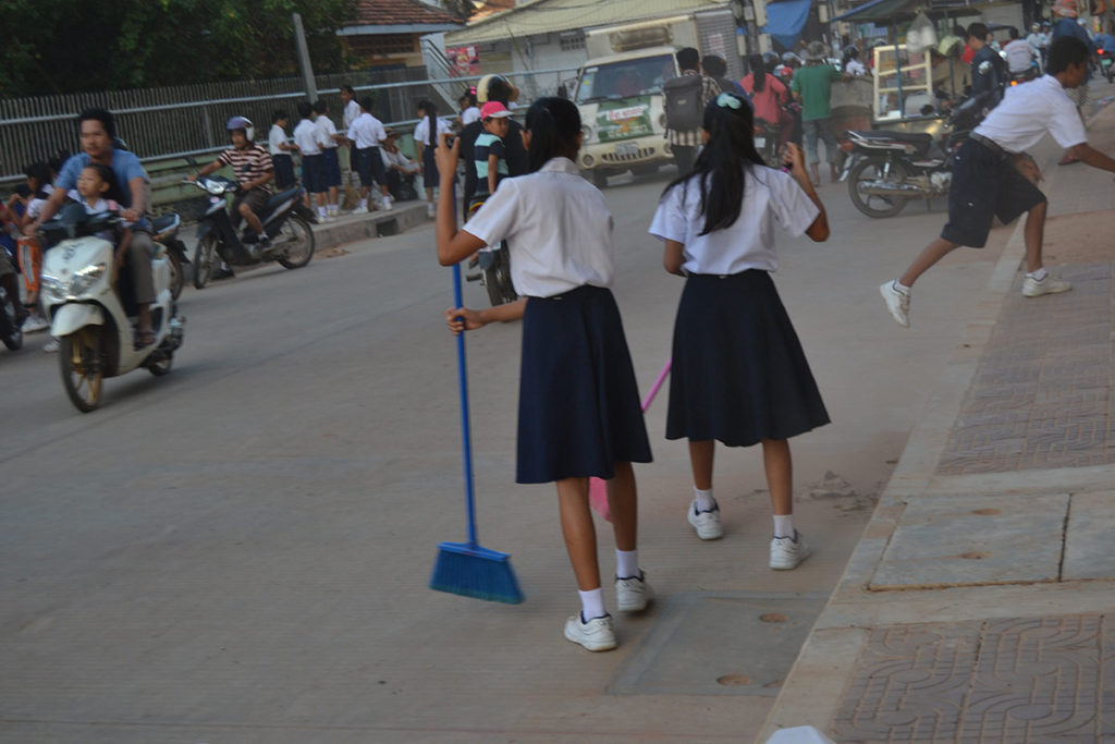Students sweeping the streets in Siem Reap